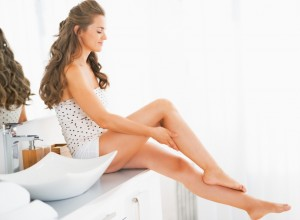 Happy young woman sitting in bathroom and checking leg skin softness
